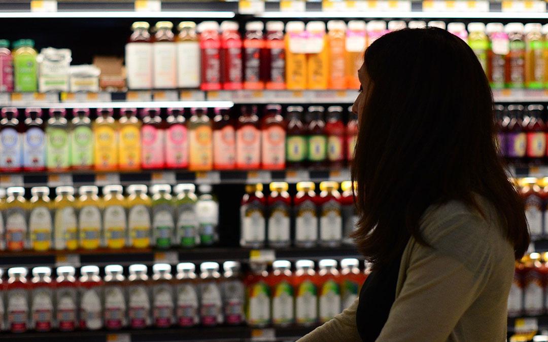 Imagen genérica de una persona en un supermercado con varios productos de alimentación de fondo./ Pixabay