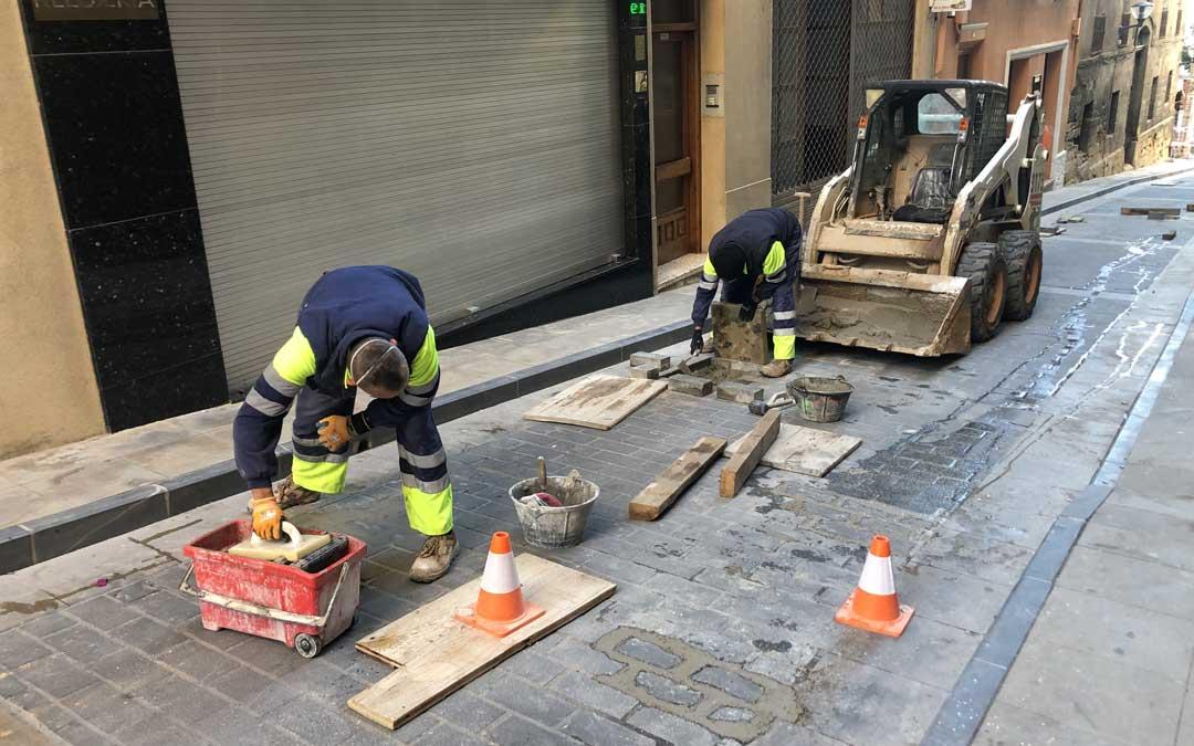 Dos trabajadores sustituyendo los adoquines de la calle Mayor / L. Castel