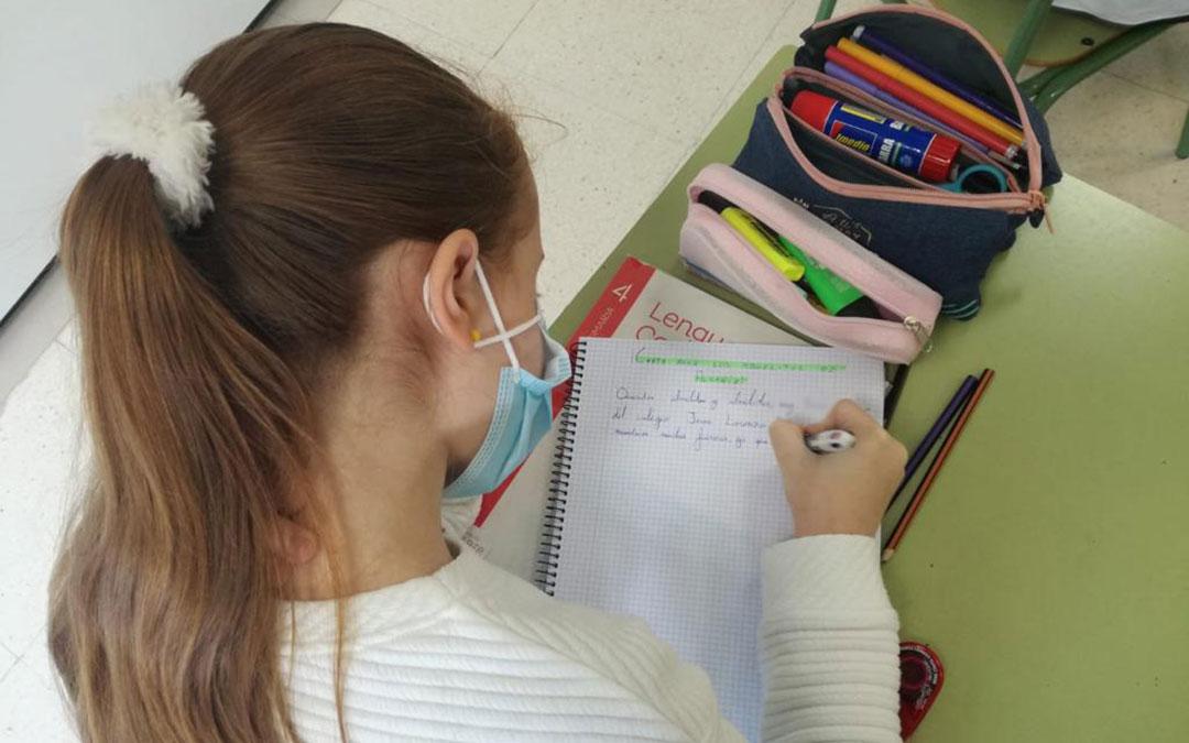 Una de las alumnas del Palmireno escribiendo la carta a una persona mayor del Santo Ángel. / CEIP Palmireno
