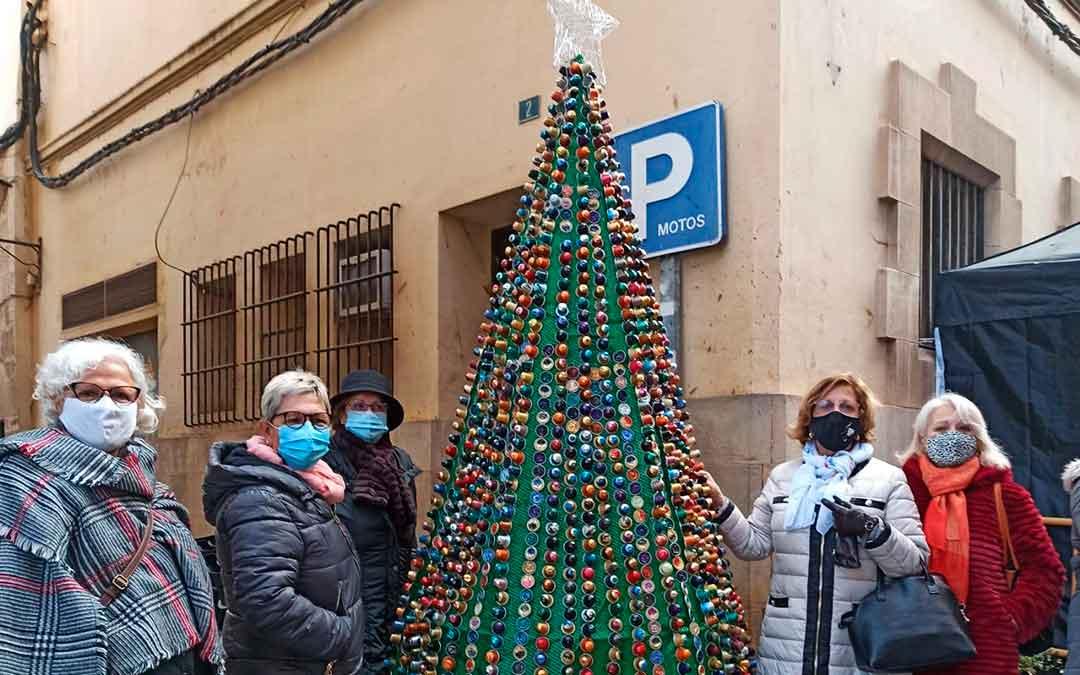 Integrantes de la Asociación de la Mujer Caspolina con uno de sus árboles reciclados.