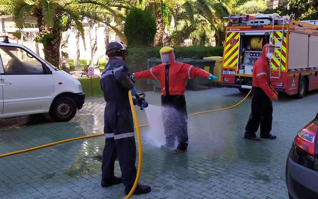 Bomberos del Parque de Caspe desinfectándose después de acceder al centro de mayores Adolfo Suárez.