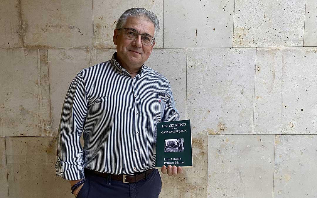 Luis Pellicer posa con su última novela, 'Los secretos de la casa embrujada'./ Alicia Martín