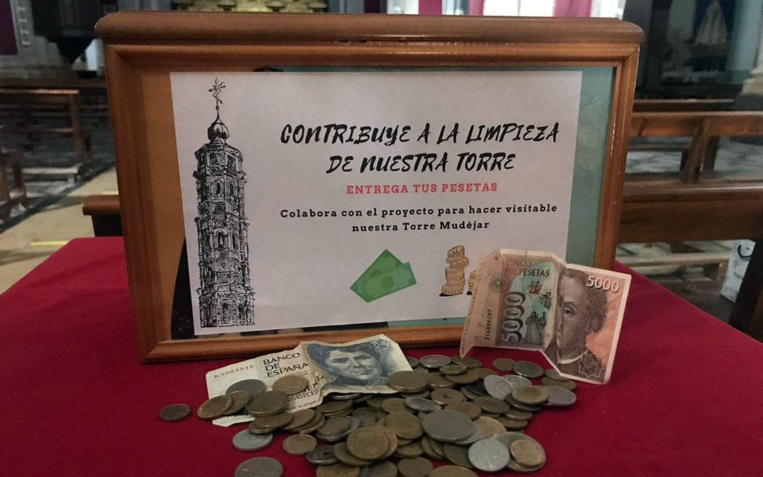 Billetes y monedas de la antigua divisa española junto al cartel de la campaña puesta en marcha en Muniesa./ L.C.