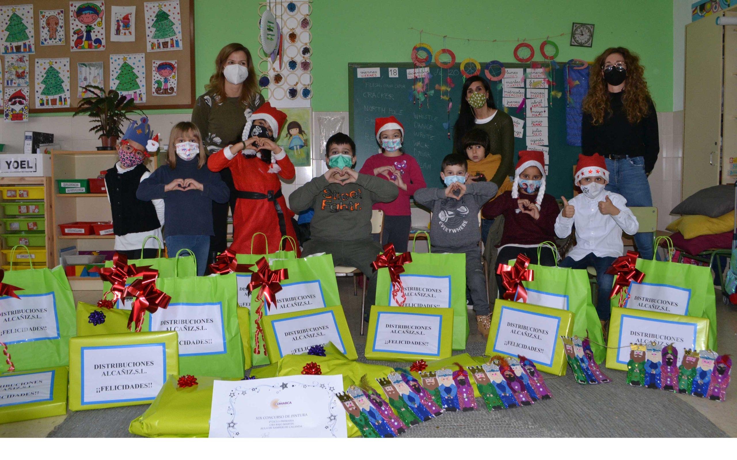 Los 9 alumnos del colegio de Samper con los regalos del concurso de postales junto a Eva Defior y María Ibañez.