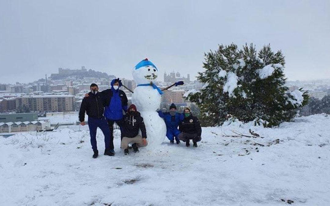 Viorel, Juanjo, Manu, Kike y Miguel con su muñeco de nieve y Alcañiz al fondo./