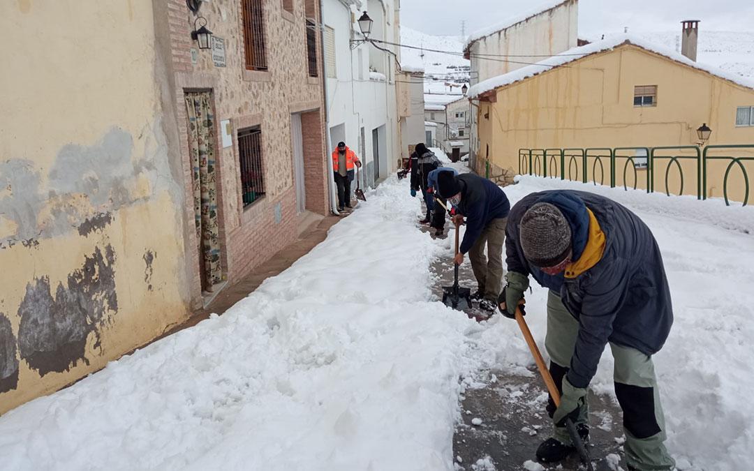 Vecinos de Ariño tirando de pala el domingo en las calles. / J. MACIPE