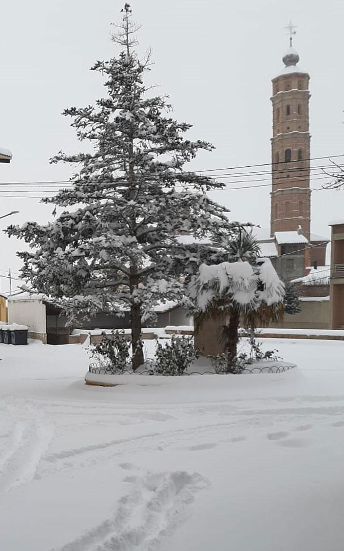 Muniesa nevada, con su torre al fondo./ Yolanda Artal