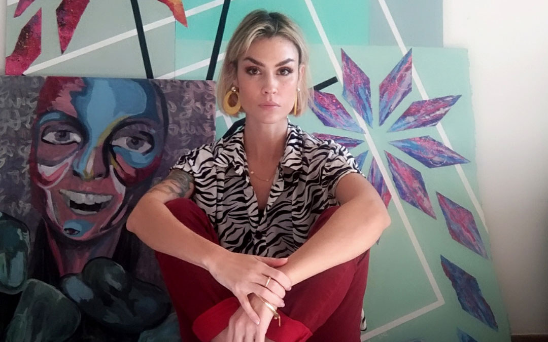 La alcañizana Sara Magallón posando con cuadros de varias etapas. El grande de detrás es de 2020 y en él ha colaborado con su madre, la pintora Merche Zagalá / S.M.