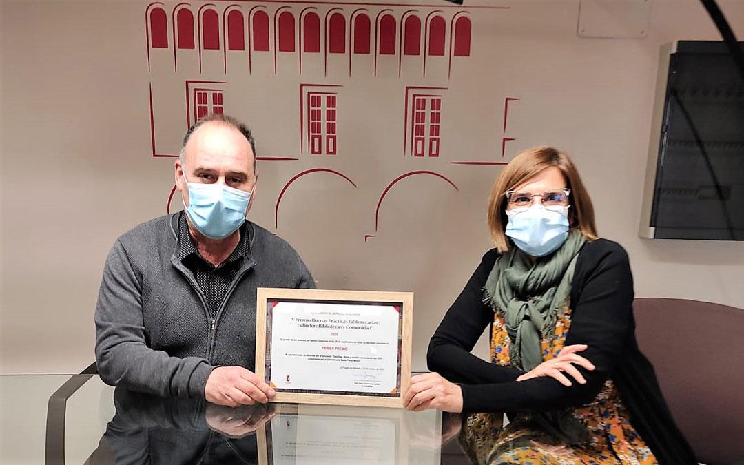 Miguel Iranzo y Maite Pérez, alcalde y bibliotecaria de Alcorisa, con el premio recibido. / Ayto. Alcorisa