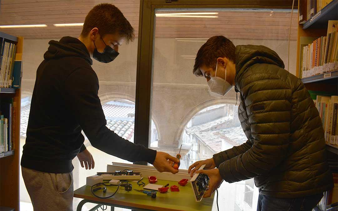 Los alumnos trabajando en la instalación de tres ordenadores en la biblioteca municipal de La Codoñera./ María Celiméndiz