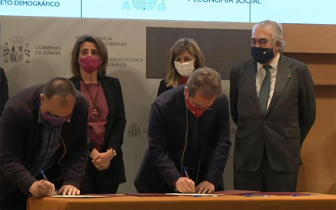 Los representantes sindicales firmando el acuerdo. Detrás, las dos ministras junto a José Bogás. / L. C.