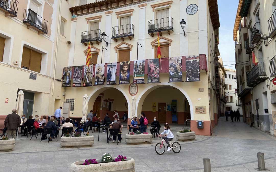 Ambiente en uno de los veladores de la plaza de la iglesia de Albalate del Arzobispo a los pies del ayuntamiento engalanado con imágenes de Semana Santa. / Alicia Martín