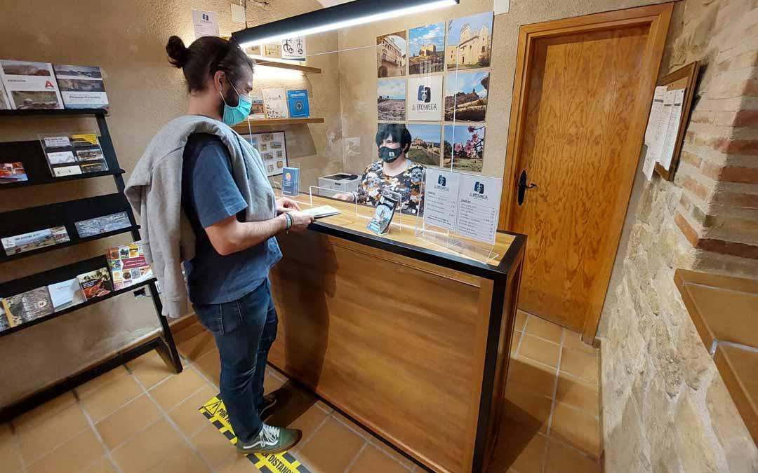 Un joven visitante zaragozano realizando una consulta en la Oficina de Turismo de La Fresneda durante la mañana del domingo. Javier de Luna.