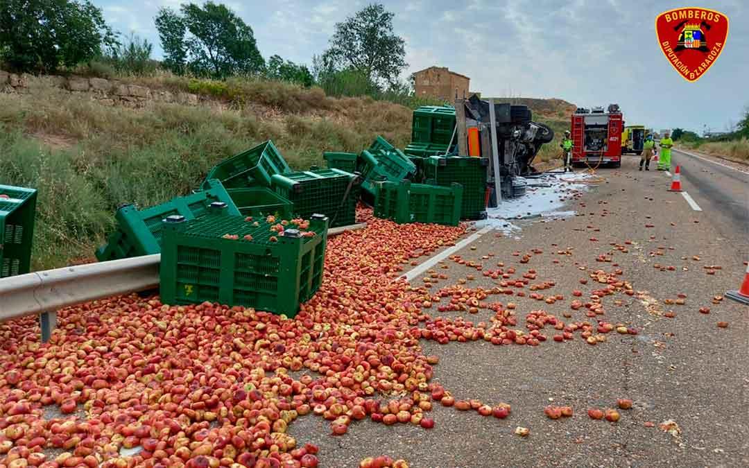 La carga del camión se ha desparramado por la carretera tras volcar el camión./ DPZ