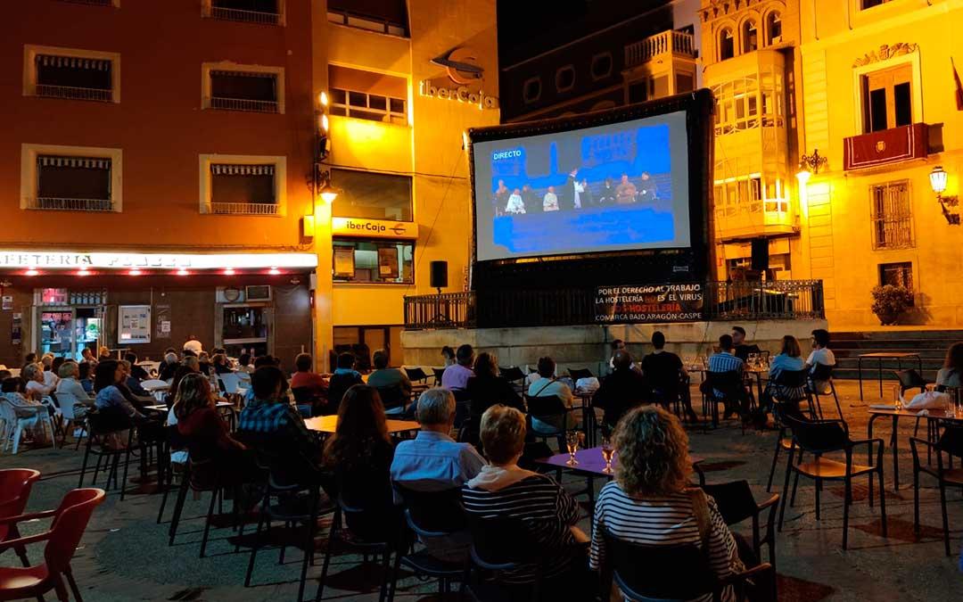 Vecinos de Caspe viendo la retransmisión del acto principal del Compromiso desde la pantalla instalada en la Plaza de España./ A.G.