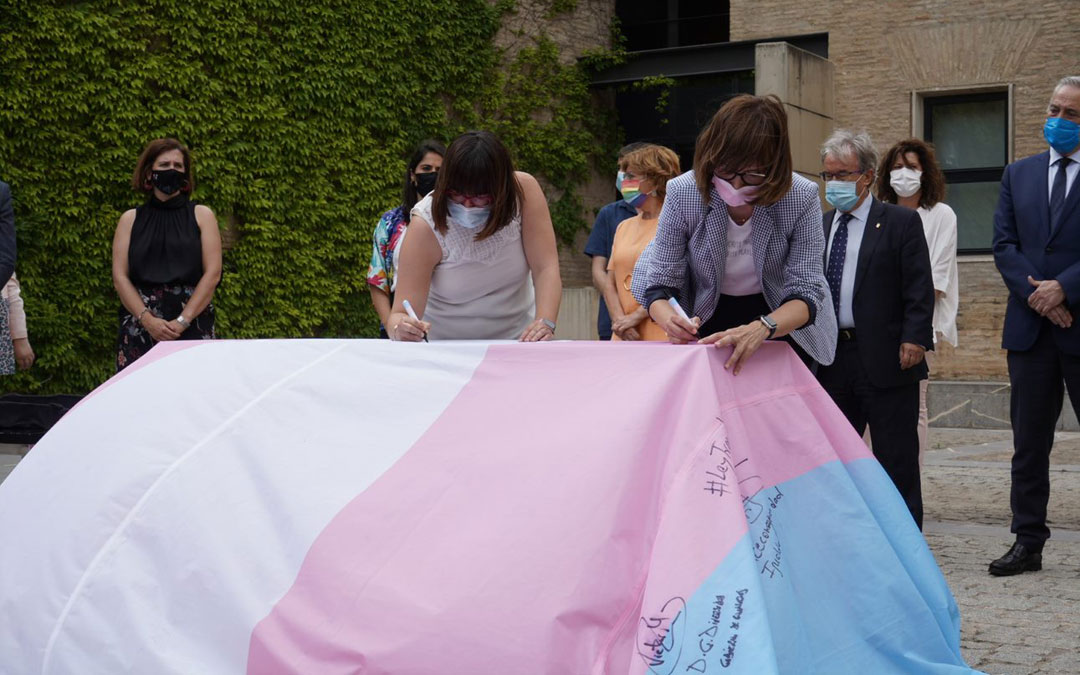 La diputada Susana Traver (izda.) firmando la bandera trans. / DPT