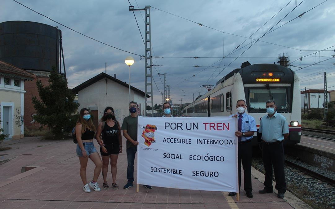 Viajeros y miembros de la Plataforma en Defensa del Ferrocarril en el Bajo Aragón Caspe frente al tren en la mañana de este lunes / Eduard Peralta
