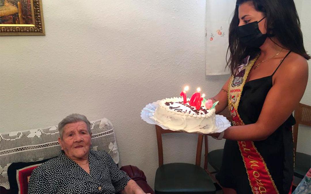 La Real Moza Alba García le entrega la tarta con las velas a Pascuala./ Olga Grau