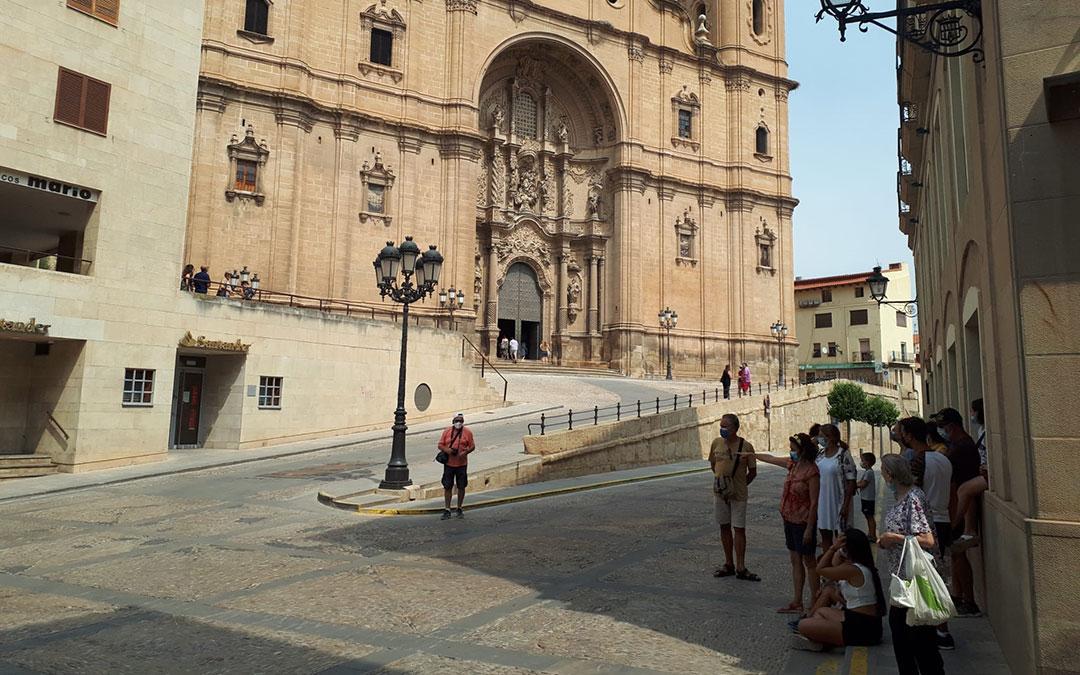 Grupo de visitantes observando la lonja de Alcañiz desde la sombra este domingo. / JAVIER VÍLCHEZ