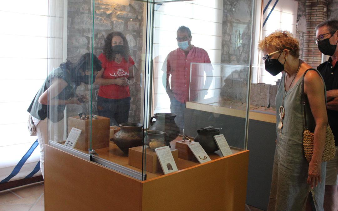 Eva Gil -al fondo junto al alcalde-, explicando algunos de los objetos recreados y expuestos. / B. Severino