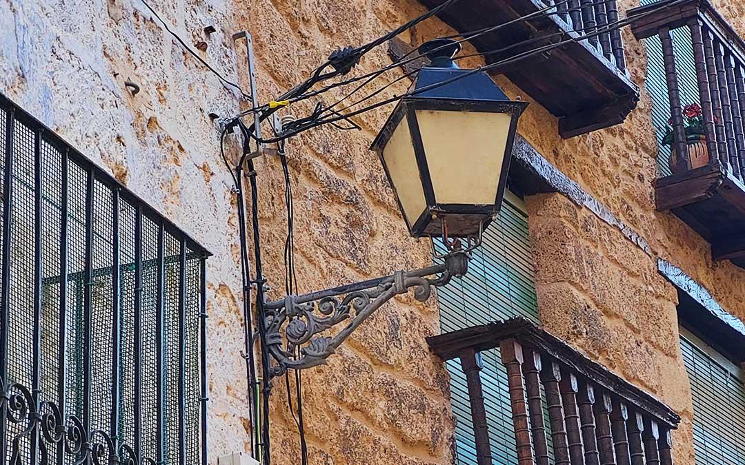 Farola en una calle con viviendas de piedra tosca y las tradicionales persianas verdes. J.L.