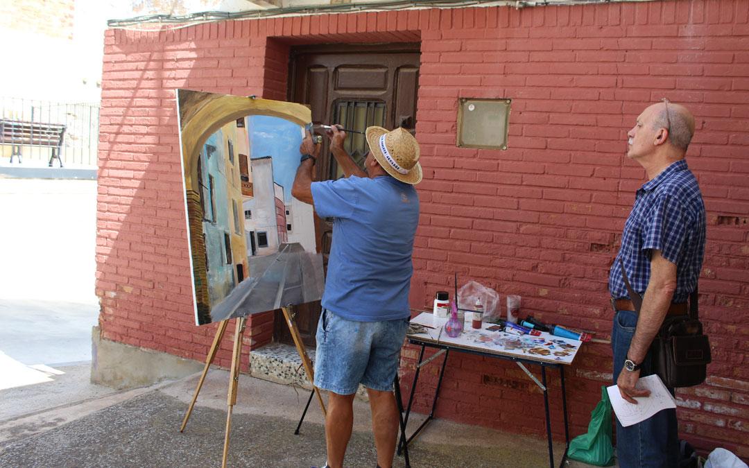 José Manuel Pinilla pinta en la esquina del Callizo Loco bajo la mirada de su acompañante Augusto Luna, ambos de Zaragoza y pintores. / B. Severino