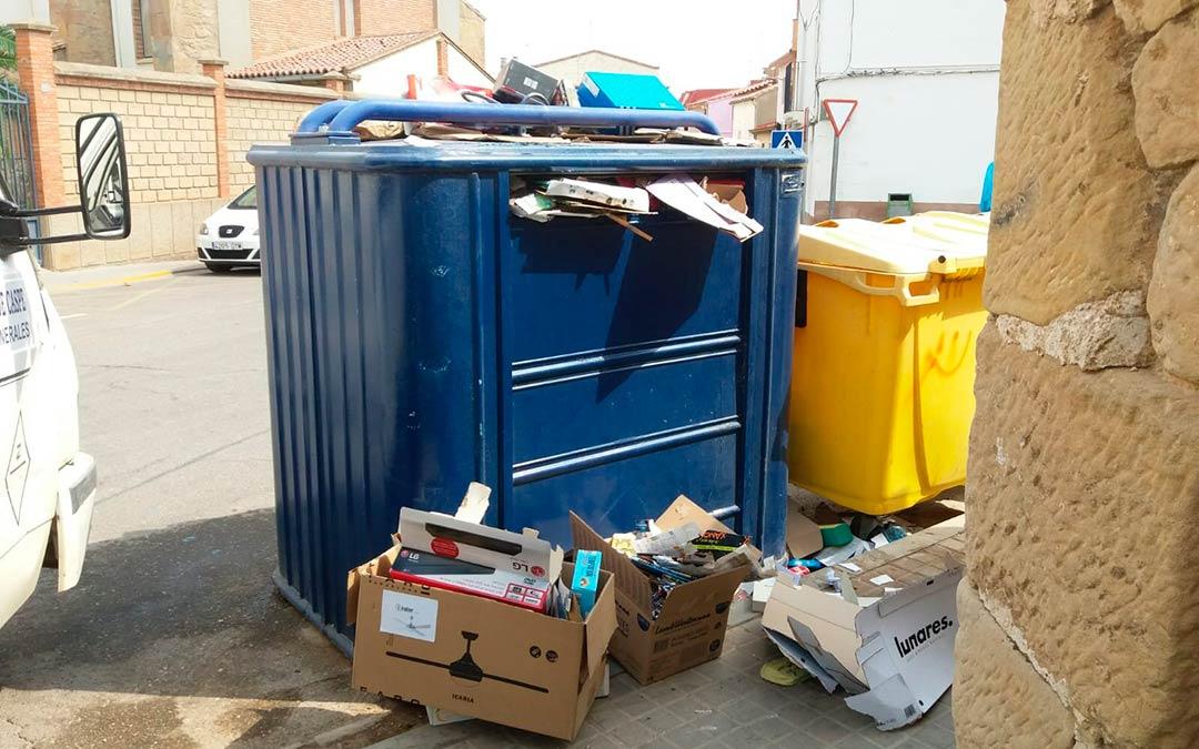 Los cartones han tenido que ser dejados en el suelo junto a los contenedores porque no cabían más dentro / Ayuntamiento de Caspe