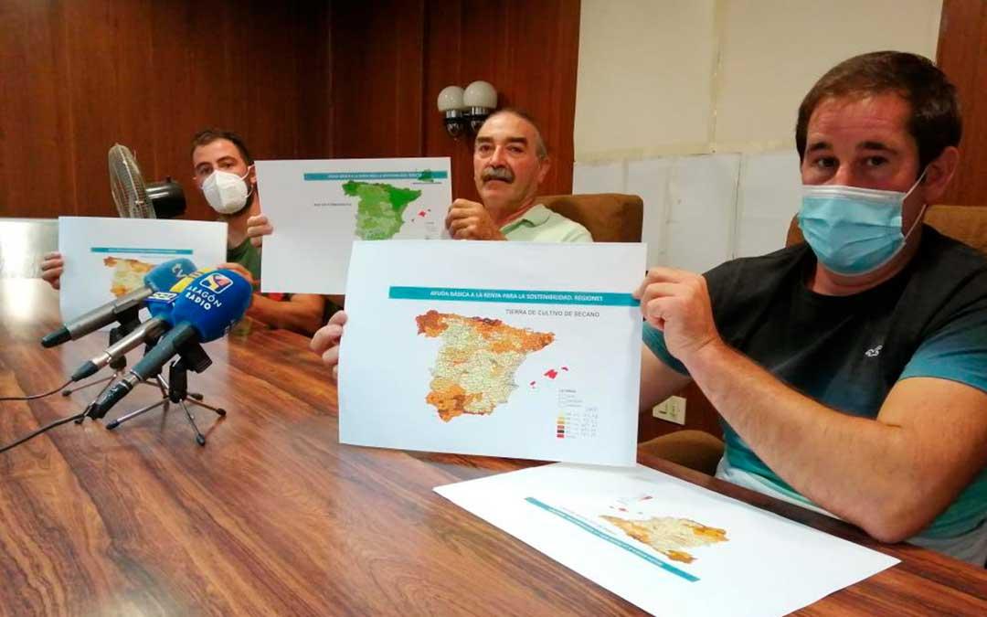 De izquierda a derecha, César Izquierdo, Ricardo Plumed y Francisco Ramo, de la plataforma Agrigate, muestran el mapa de reparto de ayudas. En color claro, las provincias cuyos agricultores percibirán menos dinero / M.A.M.