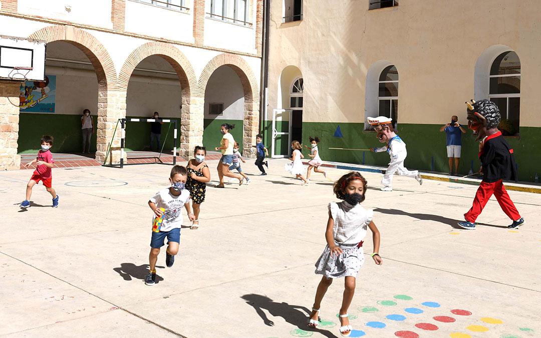 Los cabezudos corriendo detrás de los niños en uno de los patios escolares de Alcañiz. / AYTO. ALCAÑIZ